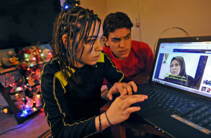 Baltimore, MD-4/8/15 - Reema Alfaheed, left, at home with her younger brother, Ahmed Alfaheed, 15, look at videos depicting the Iraq refugee camp near the border with Jordan, where they lived for six years after fleeing Baghdad. Amy Davis/Baltimore Sun Staff Photographer - #2383